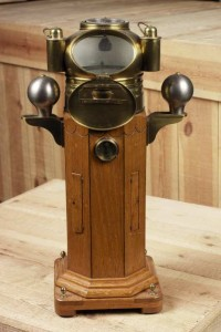 Model of a binnacle compass with polished wood body, grey soft iron adjusting balls either side and brass compass chamber above. Made by James Morton and on display in Sunderland Museum