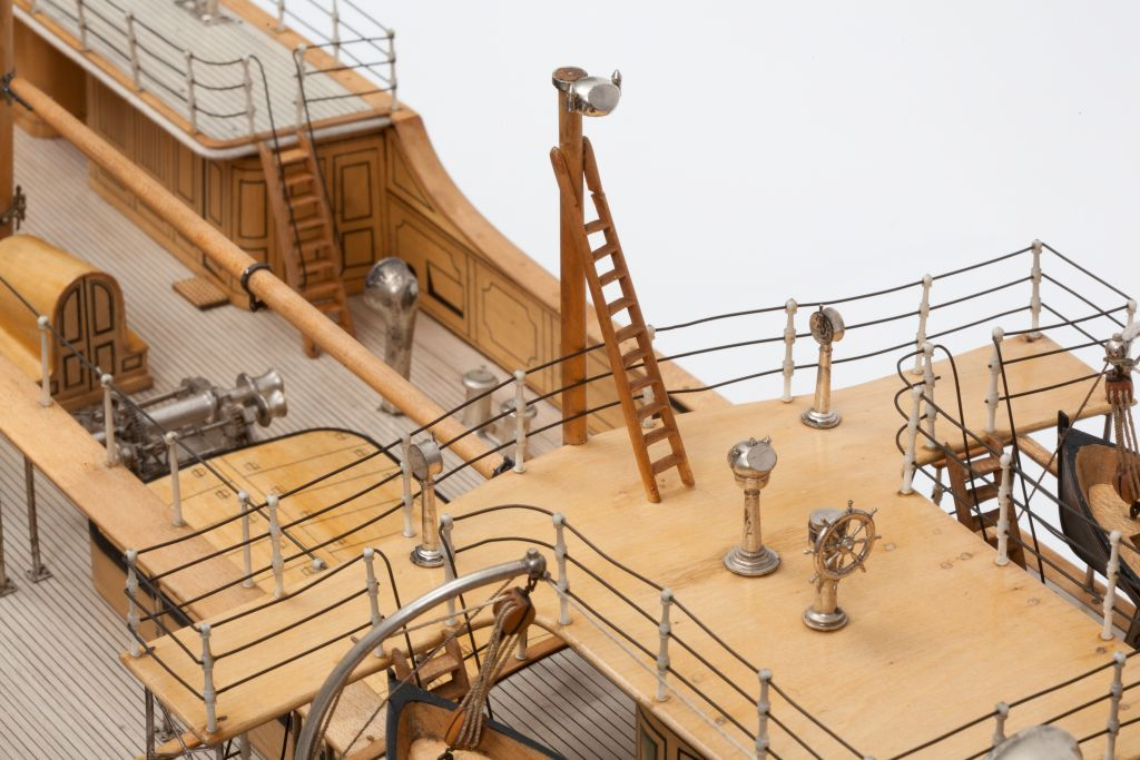 Detail of the model of ss Euterpe showing the pole compass and ladder on the bridge together with safety rails around the bridge and the normal compass binnacle and ship's wheel