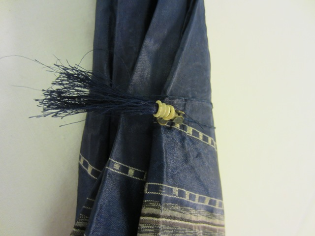 The tassel or cord was wound round the parasol and slotted into a metal catch. TWCMS:J154
