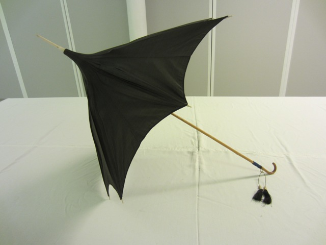 Walking parasols have longer handles and spikes. Parasol with a pagoda shaped cover in bronze shot silk, 1862 – 1870. This may have belonged to a member of the Richardson's, a Quaker family from Newcastle. TWCMS: K2195