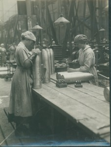 Two women workers inspecting and stamping part-finished shells.