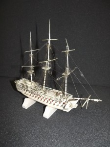 "This model of a Man o' War has been crafted from animal bone by a Napoleonic prisoner of war.  The prisoners made objects from bone, straw and wood which were easy to find, in order to produce high quality objects such as woven straw boxes and models of ships and guillotines. ""Man o' War"" was a Royal Navy term from the age of sail for a powerful warship which had many cannons.  This model represents one of the largest of these with 104 guns on three decks, although it is not modelled on any particular ship. The model was very badly damaged; the masts had broken and had detached from the model, and much of the rigging was broken and tangled.  The masts have been put back into position using a two-part adhesive, and the rigging has been repaired and replaced, but only where it has been possible to identify where the original rigging would have been."