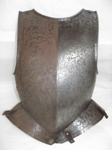 "Breast plate from a suit of armour possibly dating back to the 15th century.  The breast plate is decorated with a floral pattern like the ""mantling"", or drapery, of a coat of arms.  The decorative design is completed by a knight in a full suit of armour and a mythical phoenix. The breast plate was covered in a heavy layer of red iron corrosion which was disfiguring the surface of the armour and if left could have led to extensive damage. For the purpose of this display the corrosion has been removed from one half of the breast plate, and it has been left in place on the other half in order to highlight the difference.  The corrosion will be completely removed from the breast plate when the armour is removed from this display."