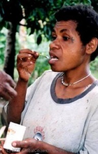 Woman using betel flower to scoop lime, PNG.