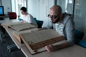 Volunteers reading First World War era newspapers at Newcastle City Library