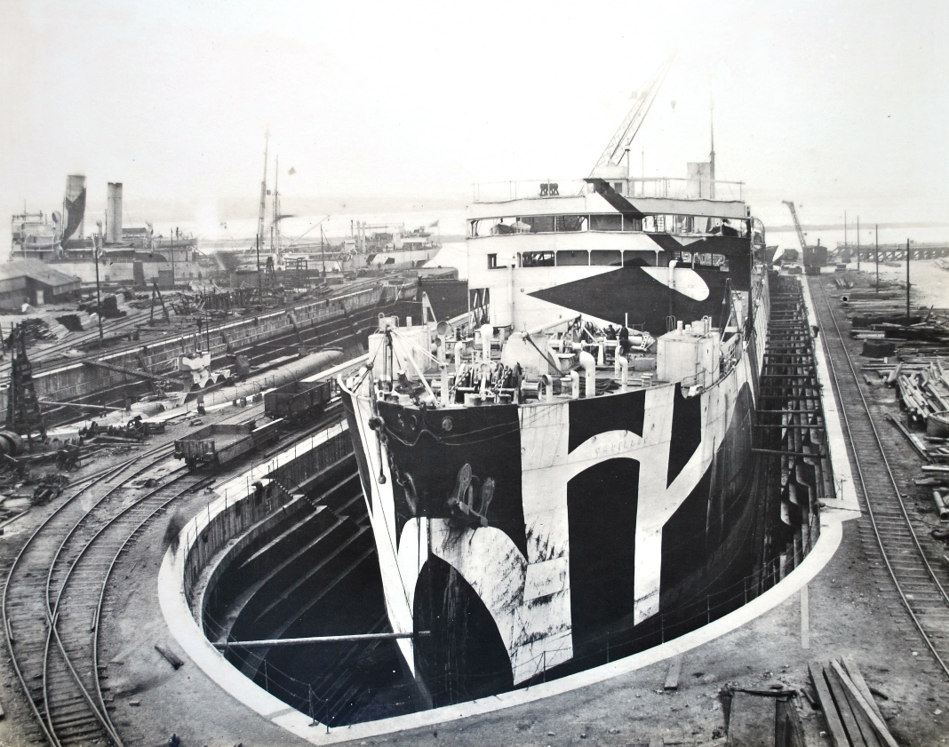 Photograph of dazzle painted oil tanker Cadillac undergoing repairs at Smith's Dock yard at North Shields on the River Tyne. Cadillac was built by Palmer's Ship Building & Iron Co. Ltd., Hebburn-on-Tyne and completed in December 1917. On 7th April 1918 she was torpedoed and damaged by U-53 about 100 miles WSW of Bishop Rock. Cadillac was one of Wilkinson's dazzle ships that made port after a U boat attack. I think it is a fair bet that the repairs are for the damage caused by U-53's torpedo. (TWCMS : 1993.9590 – Smith's Dock Notable War Jobs album)