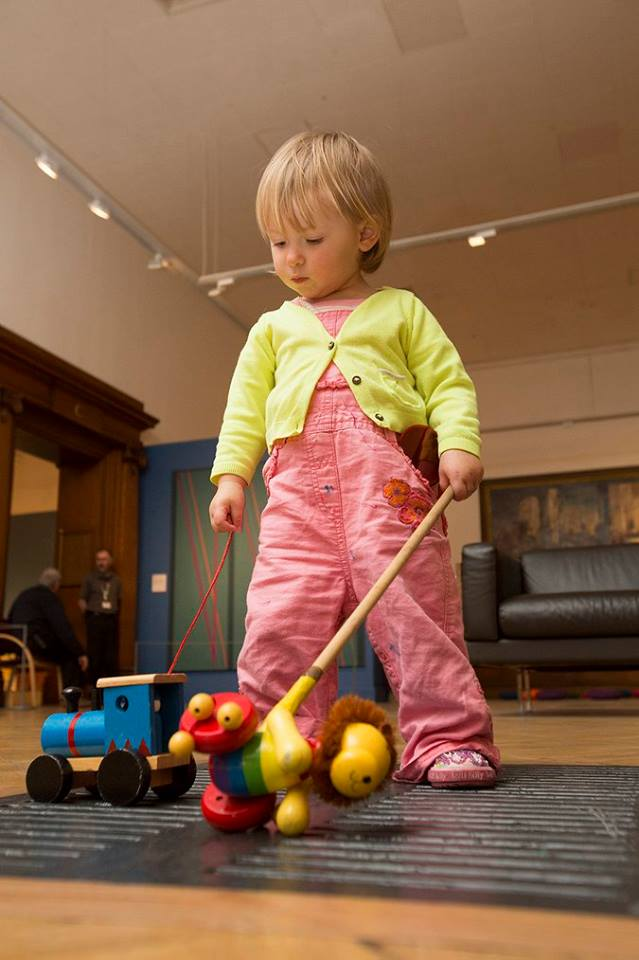 Coloured paddles are close at hand in the pocket of this Explorer's dungarees as she navigates the gallery.