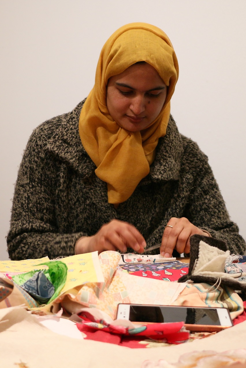 Woman in headscarf and coat working at table full of fabric pieces
