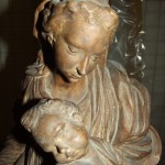 Brown wooden sculpture of woman holding small child