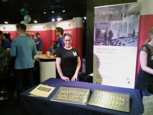 Woman standing at indoor stall promoting Hatton Gallery
