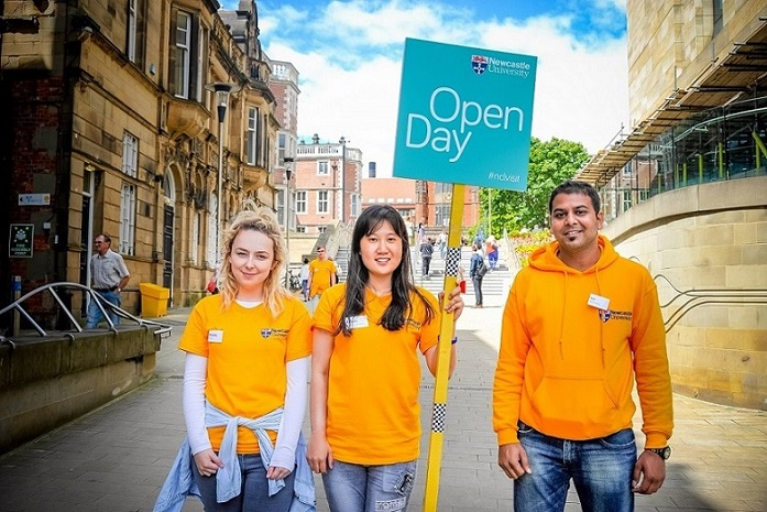 Three students in orange t-shirts with Open Day placard on campus