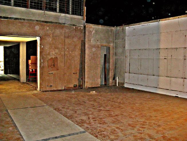 Corner of bare room inside building site with wooden floor plus partial doorway