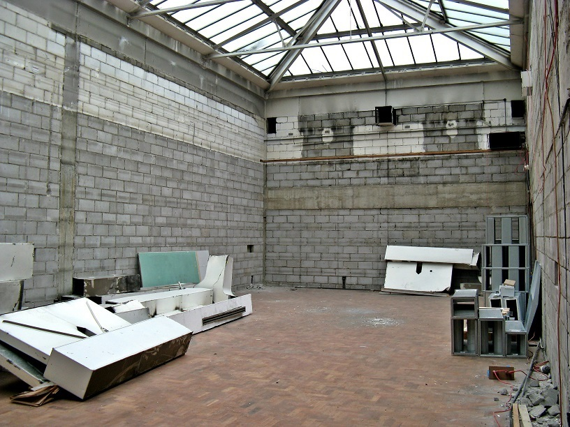 Large bare interior, breezeblock walls, clear glass roof, piles of building rubbish