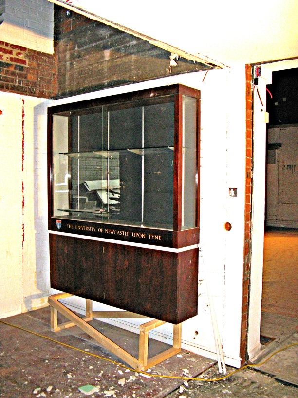 Large wooden and glass display cabinet on wall of building site interior