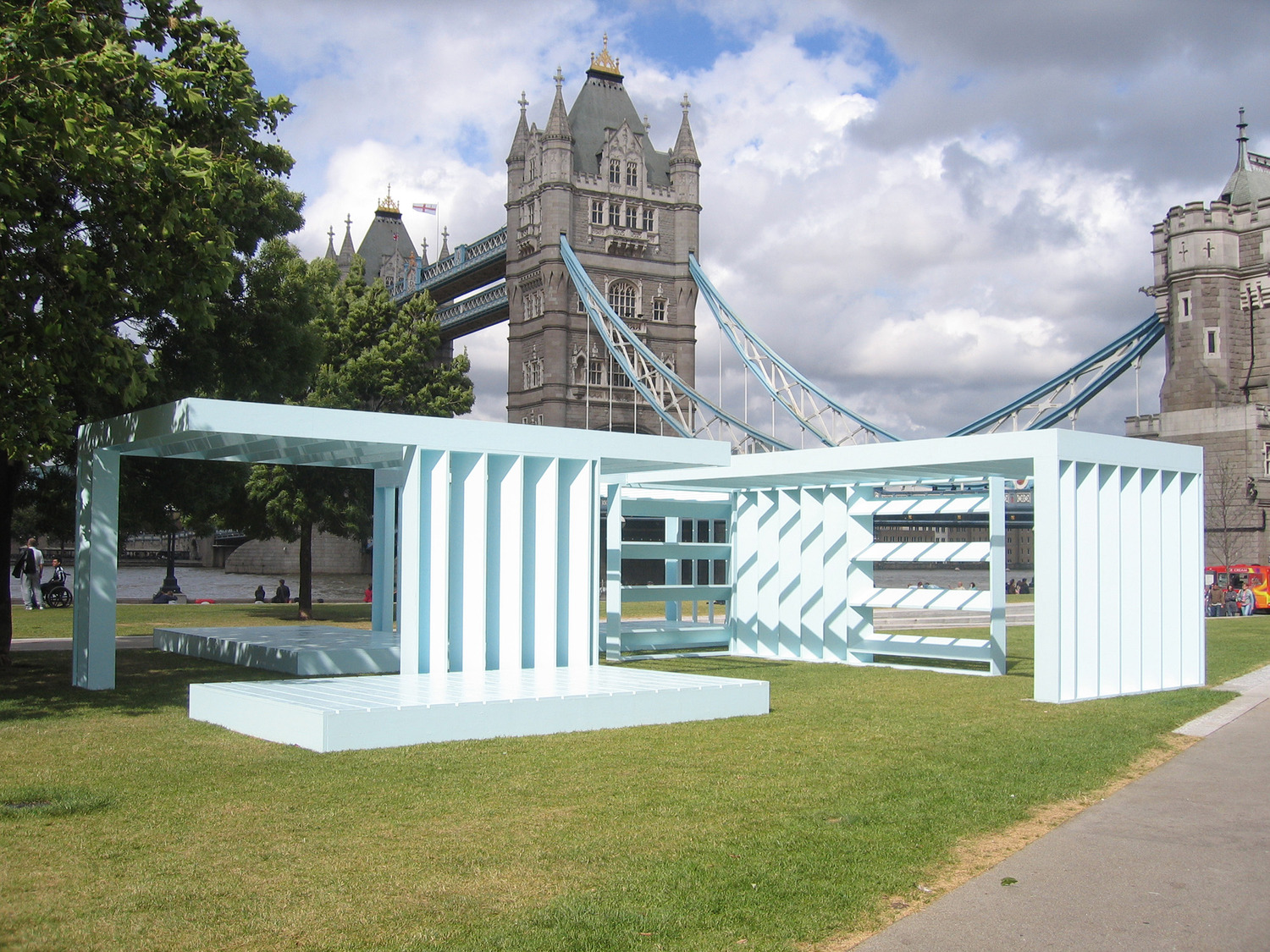 External photo of large light-blue abstract structure sitting on grassed areas with London Twoer Bridge in backcround