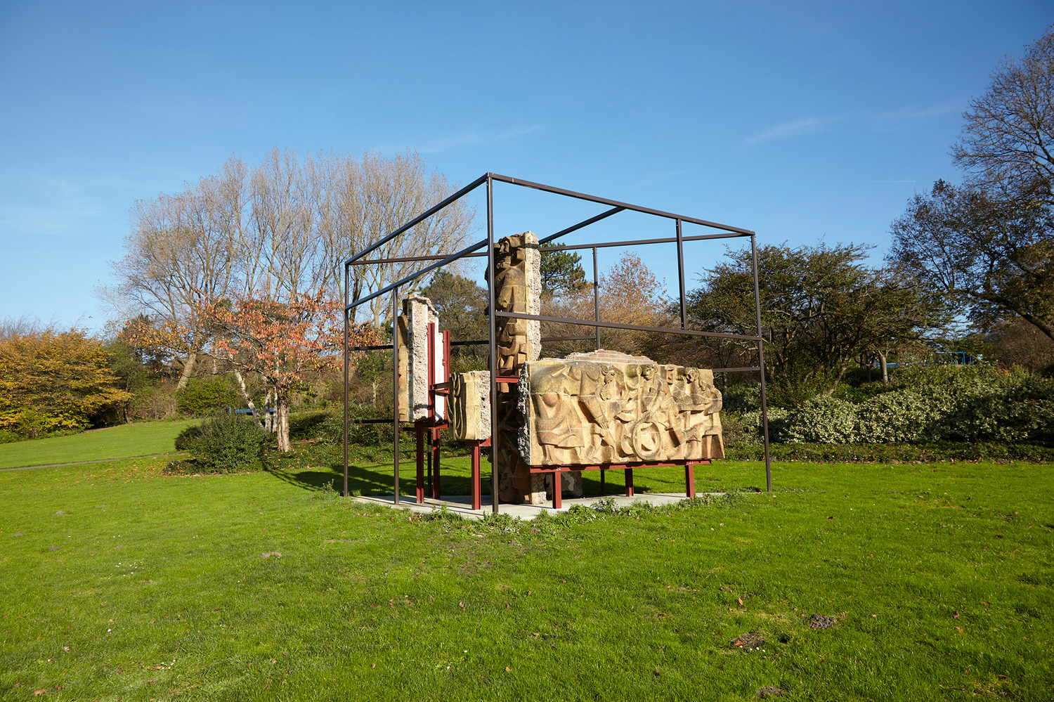 External photo of abstract structure comprising stone walls set within a steel framework, located in parkland of grass and background trees