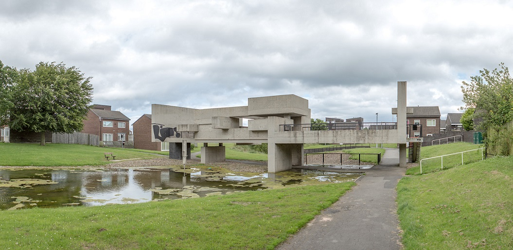 External photo of large abstract building consisting of concrete blocks , set across a pond in a setting of open grass area and surrounding houses
