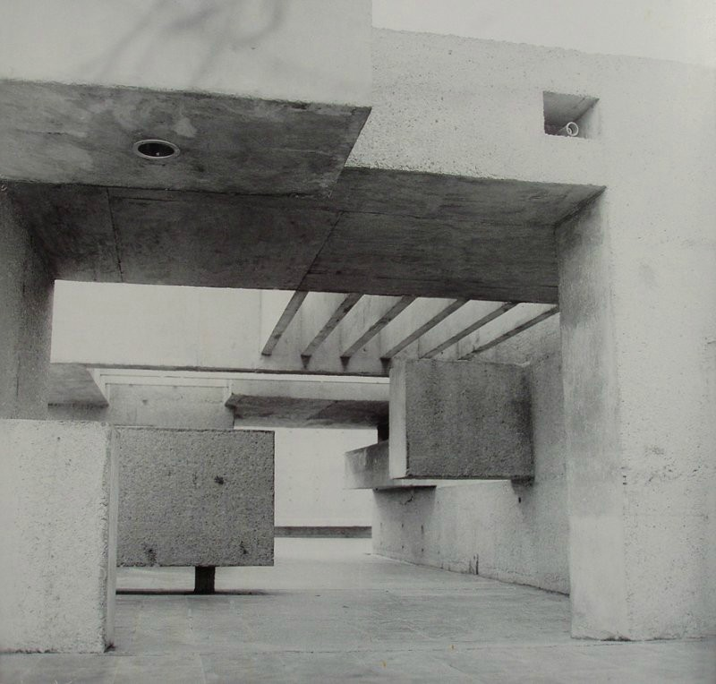 Black and white photo of large abstract structure comprising several concrete blocks and crossbeams