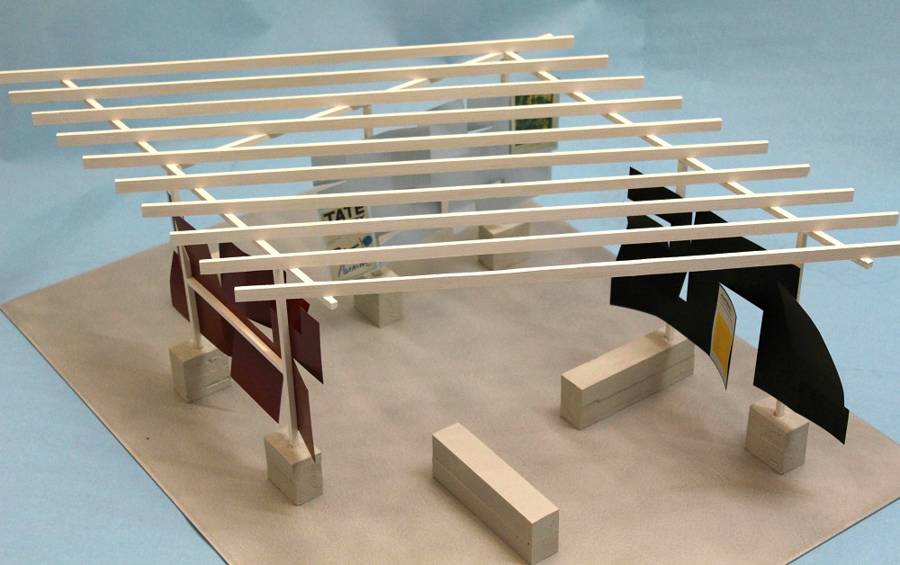 Overhead view of model of open abstract structure comprising several blocks supporting framework with roof of crossbeams