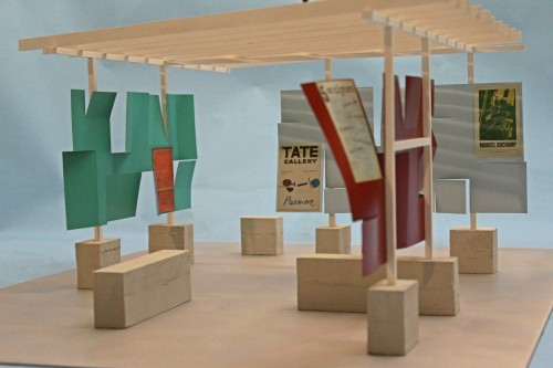 Model open structure with blocksand vertical uprights supporting a roof of crossbeams against blue background - also displaying several small posters within model