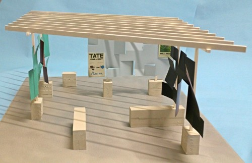 Model open structure with blocksand vertical uprights supporting a roof of crossbeams against blue background