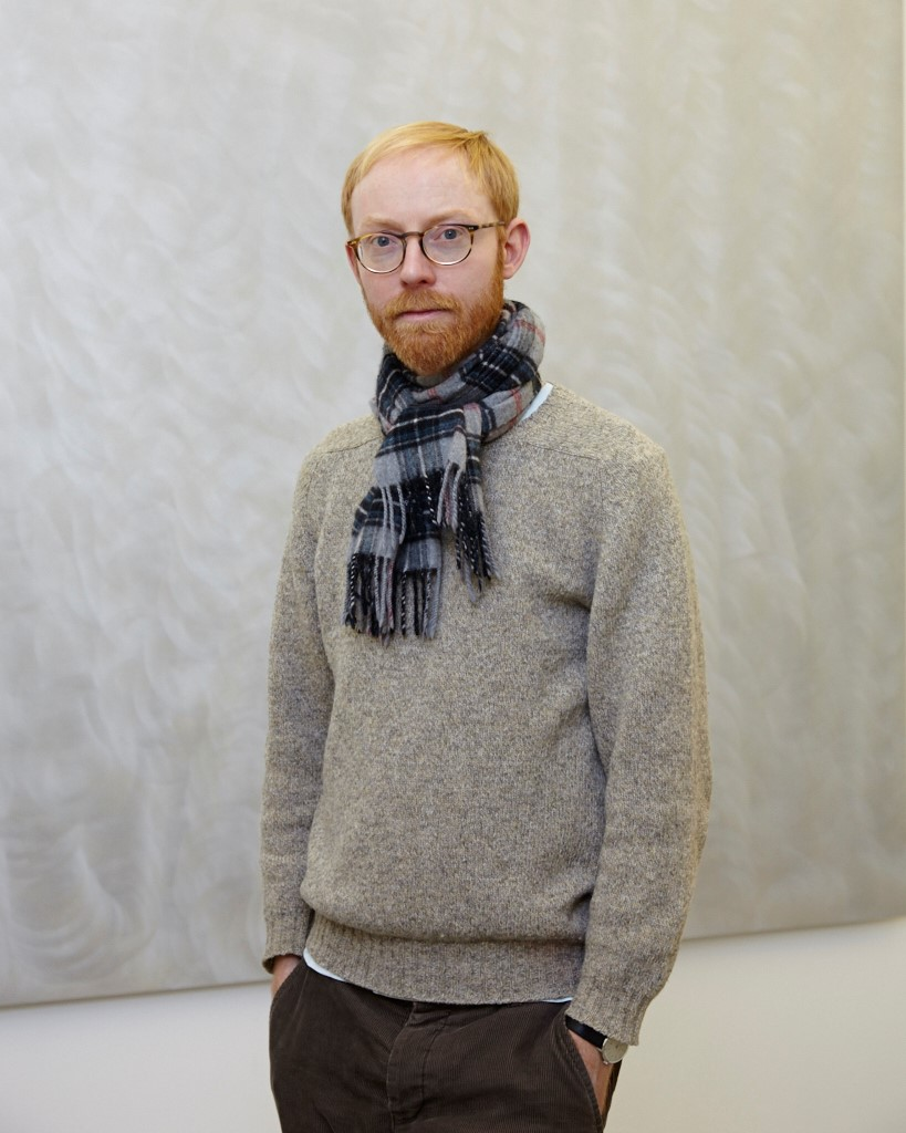 Mid-shot photo of male, slim, red hair, grey sweater and wearing blue tartan scarf against grey background