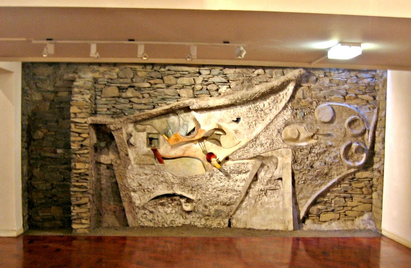 Interior setting of large abstract wall sculpture set on a wall of slate stones, with wooden roof beam across top of picture and wooden flooring in foreground