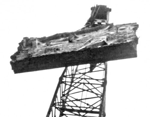 Black and white old photo of large abstract wall sculpture being hoisted into the sky by a large crane