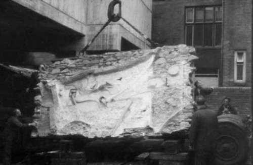 Old black-and-white photo of large abstract square wall sculpture being lifted off a the back of an open truck by a lifting hook and strap