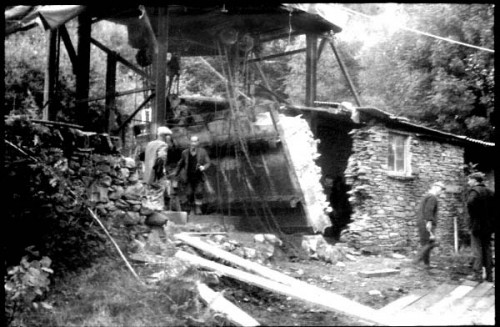 Vintage black and white exterior photo of group of men removing a large section of wall from a smallstone outbuilding