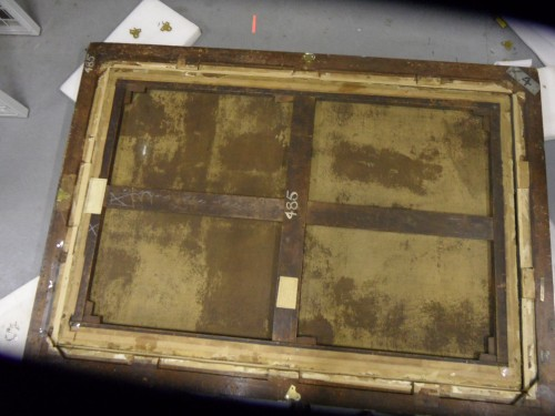 Secondary support (stretcher) • The canvas is attached to a large Square (bute) jointed stretcher with a solid horizontal crossbar and a two-part vertical crossbar. This is unlikely to be original to the painting as expanding stretchers as canvas supports were not used before the 18th c • All of the keys are present and tied in. • The stretcher has been expanded by about 4 mm on each corner • It's in good condition with only a slight bowing on the two verticals. • There are two exhibition labels attached to the stretcher bars one for the Royal Academy in London for the winter exhibition of 1962 and another one for the Graves Art Gallery Sheffield for an exhibition of Dutch masterpieces in 1956 • On the back board there is a second exhibition label from the National Gallery for an exhibition called Paradise which was more recent. • The Shipley Art Gallery is chalked on the central bar with what is possibly an old accession number 485 (also written on the frame.) Canvas • The original canvas is a medium weave which has been lined on to a fine close weave canvas with a wax resin lining. • None of the original turnover edges remain. • There is considerable bleed through in patches on the back of the lined canvas indicating that it was hand lined. See photo • There are splash marks on the back of canvas on the left-hand side. • There are dark spots on the back of the canvas particularly noticeable in the lower section indicating that the canvas has probably been damp at some points with possible mould growth. • There is a small repair visible on the back of the canvas in the top right hand quadrant which corresponds to a slight indent on the front of the painting. • The canvas is attached to the stretcher with rusted iron tacks and brown gummed tape.