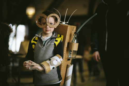 A photograph of a young child enjoying cardboard crafts at Dsicovery Museum