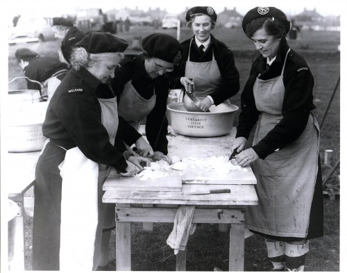 Newcastle Civil Defence volunteers preparing a meal in a camp kitchen