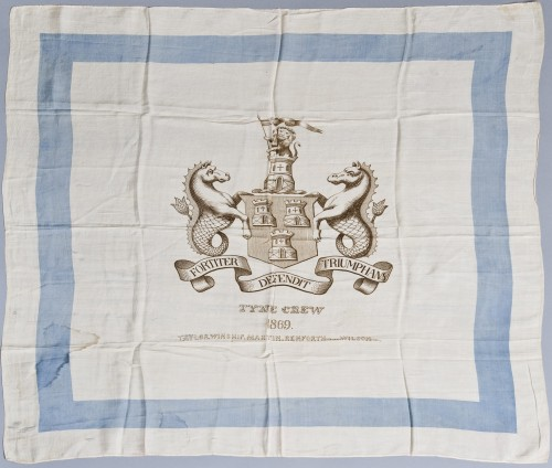 Rowing Colour of the Tyne Champion Four 1869. This colour was issued to mark the home and home races of the Tyne Crew, against a London crew, in the autumn of 1869. It features the Newcastle coat of arms and lists the Tyne Crew, (James) Taylor, (Thomas) Winship, (John) Martin, (James) Renforth (Stroke), (Thomas) Wilson (cox). The Tyne men won both races with the boy coxswain Wilson distinguishing himself on each occasion. TWCMS : 2011.3448. Discovery Museum